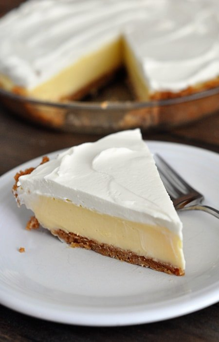 A slice of whipped cream topped, graham cracker crust lemon pie on a white plate with the rest of the pie in the background.