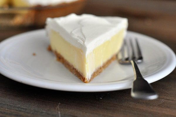 A slice of whipped cream topped, graham cracker crust lemon pie on a white plate.