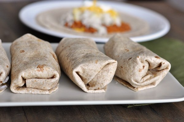 burritos lined up in a row on a white platter