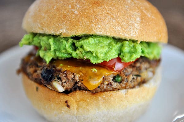 A jalapeno cheddar burger topped with guacamole and tomato slices on a white plate.