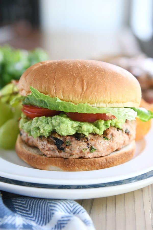 jalapeno turkey burger with guacamole, tomato, and lettuce on white plate