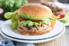jalapeno cheddar turkey burger with guacamole, tomato, and lettuce on white plate