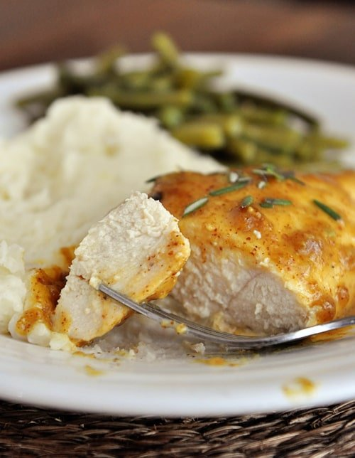 mustard covered chicken breast with a bite cut next to mashed potatoes and green beans on a white plate