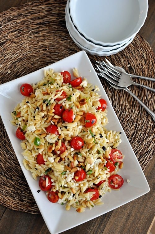 A white dish full of cooked orzo pasta, cherry tomatoes, pine nuts, and basil, with 3 forks and some white bowls on the side.