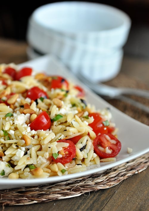 A white dish full of cooked orzo pasta, cherry tomatoes, pine nuts, and basil, and some white bowls and forks on the side.