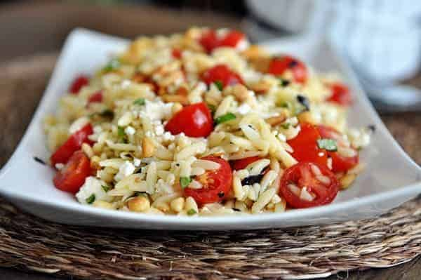 A front view of a white dish full of cooked orzo pasta, cherry tomatoes, pine nuts, and basil.