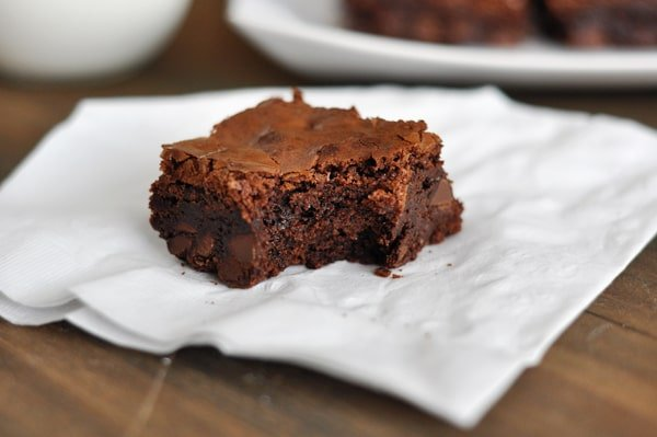 a brownie with a bite taken out of it sitting on a napkin