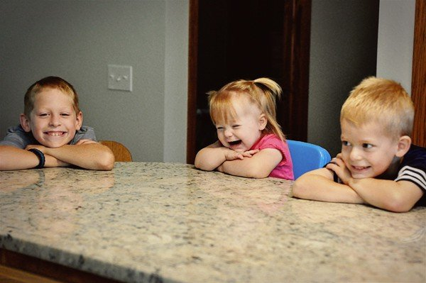 three little kids leaning their heads on a counter and smiling