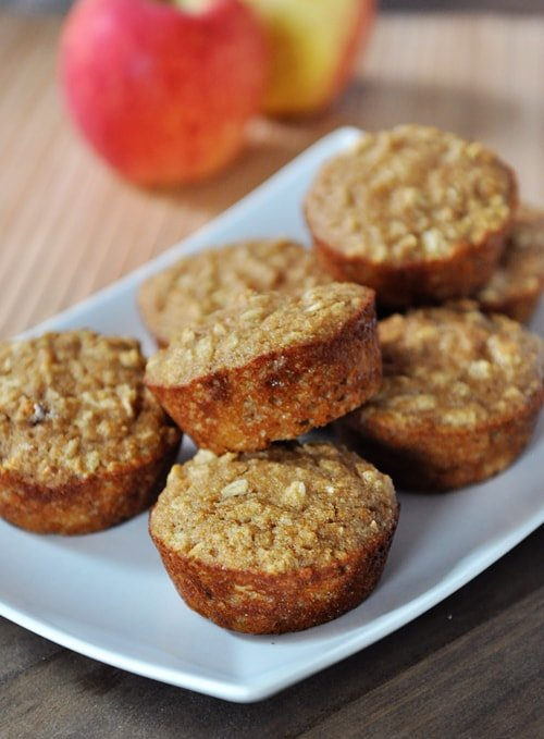 A white platter full of baked muffins, studded with oats, and apples in the background.