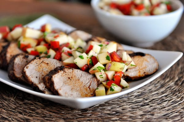 white platter with slices of grilled pork loin topped with fresh apple salsa