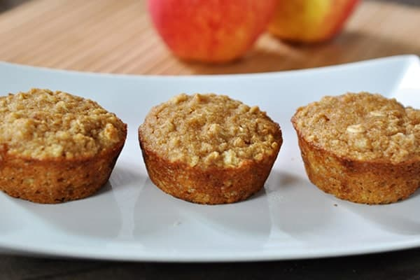 A white plate with three baked muffins, studded with oats, and apples in the background.