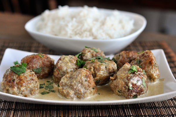 white dish with browned meatballs covered in sauce and parsley and a dish of cooked white rice behind it