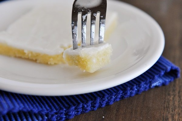 a piece of white Texas sheet cake on a white plate with a fork taking a bite out