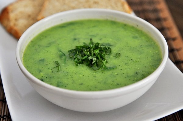 white bowl full of green soup topped with chopped chives