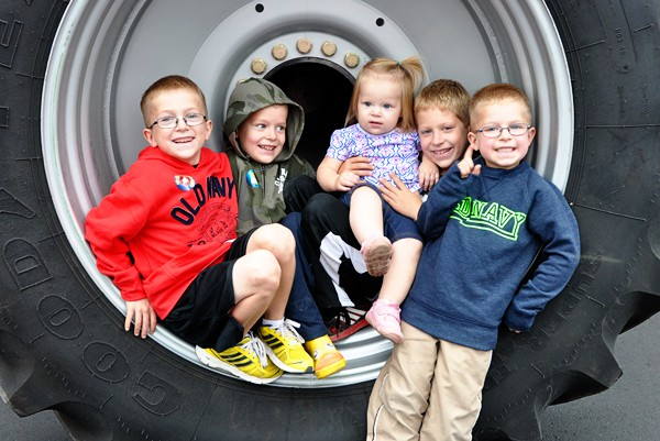 five little kids sitting inside the rim of a giant tire