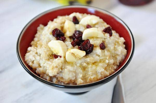 a bowl of cooked steel cut oats topped with banana slices and cranberries
