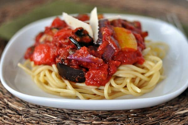 white plate with cooked spaghetti noodles topped with a chunky red sauce