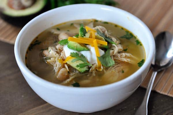 white bowl of white bean chicken chili with sour cream, diced avocado, and cheese