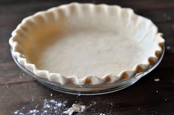 A raw crimped pie crust in a glass pie pan.