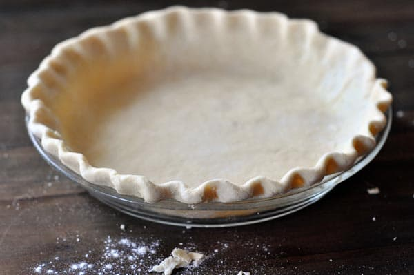 uncooked crimped pie crust in a glass pie dish