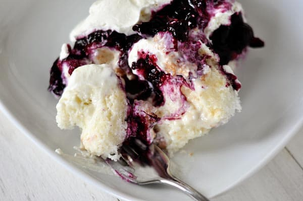 A plate of white cake, mixed with blueberry sauce, and whipped cream.