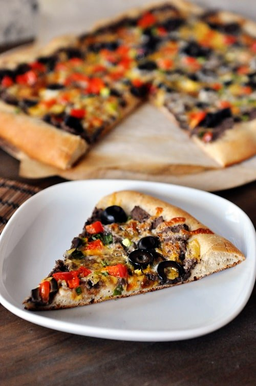 a slice of black bean veggie pizza on a white plate with the rest of the pizza behind it