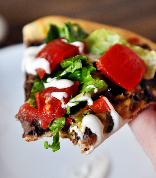 a slice of black bean pizza with a bite taken out and lettuce and tomatoes on top