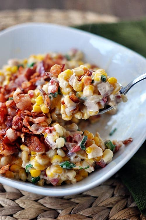 A bowl of creamy confetti corn and bacon with a spoon taking one big bite out.