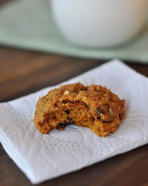 a chocolate chip pumpkin oat cookie with a bite taken out on a napkin