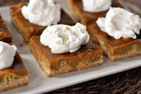 pieces of pumpkin pie sheet cake with whipped topping on top on a white platter