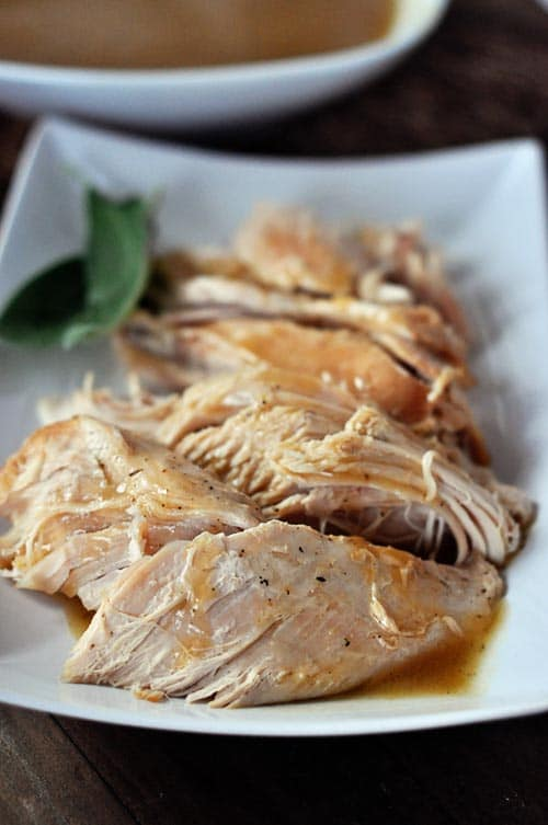 a cut up turkey breast with gravy over the top on a white platter