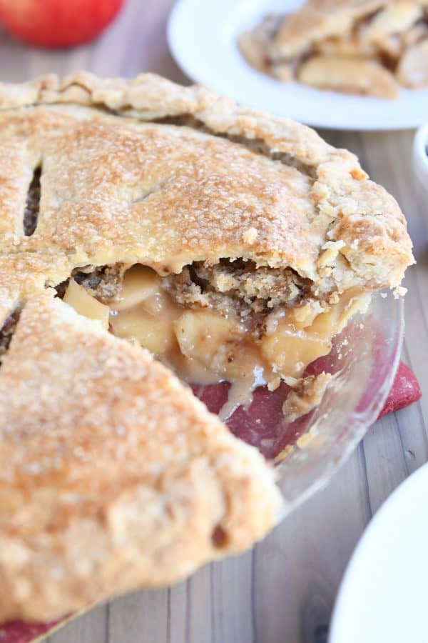 toffee crumble caramel apple pie in glass pie plate with slice removed