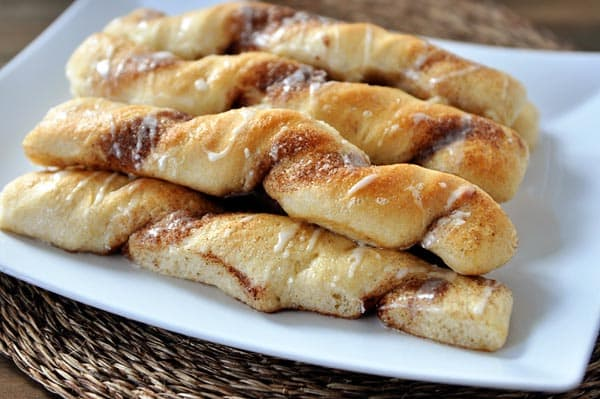 white platter with stacked cinnamon and sugar breadsticks