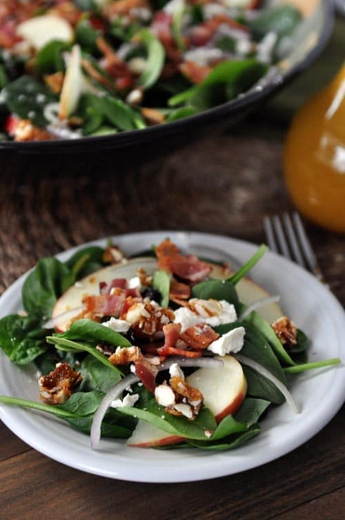 A plate of spinach salad with chopped nuts, onions slices, bacon, apple slices, and feta on top.