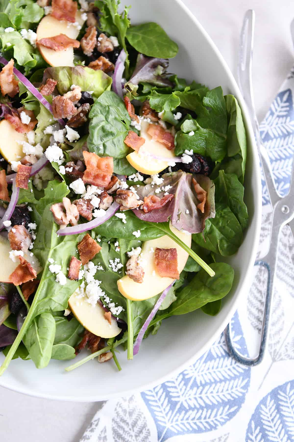 top down view of spinach salad in white bowl