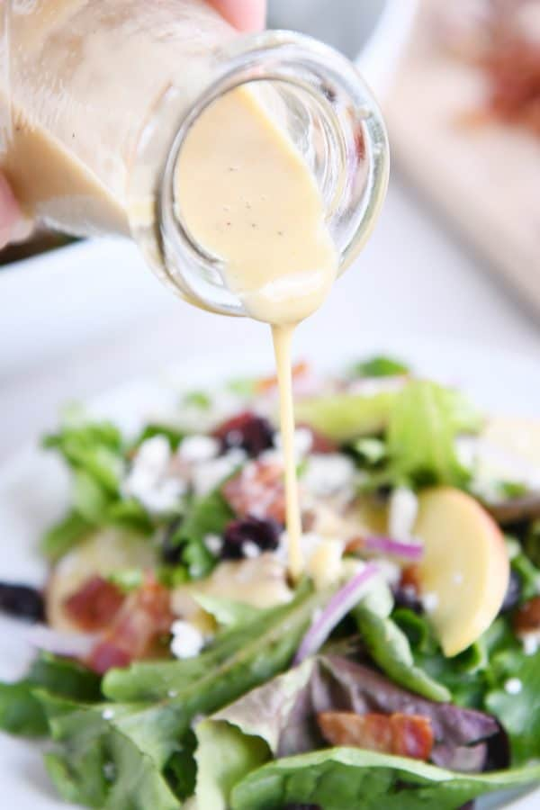 pouring vinaigrette over amazing spinach salad