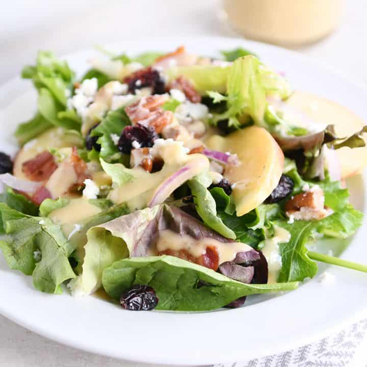 dished up portion of spinach salad on white plate with vinaigrette, bacon, onions and feta