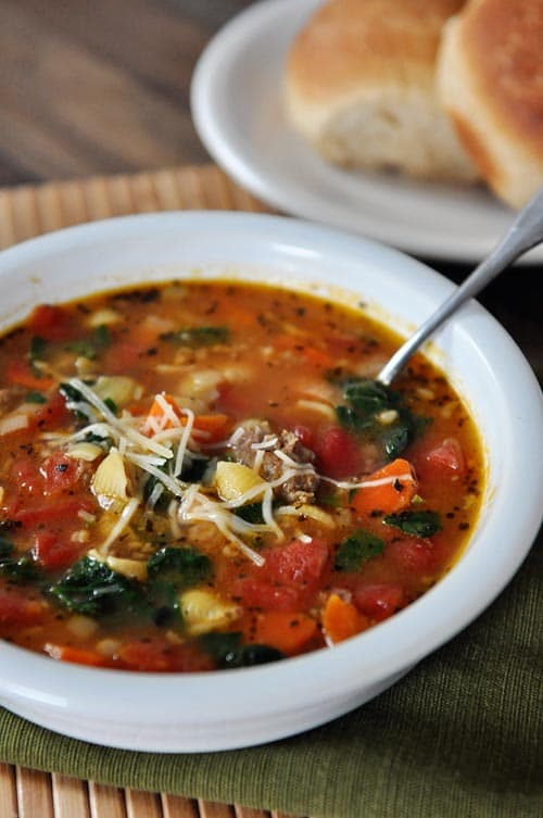 white bowl full of Tuscan sausage soup full of pasta, spinach, and tomatoes.