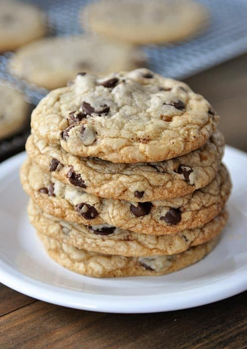 stacked chocolate chip cookies on a white plate
