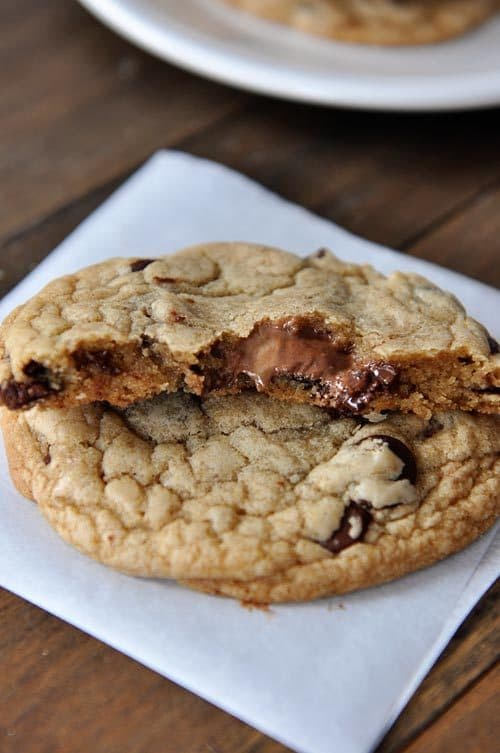 two Nutella and peanut butter stuffed chocolate chip cookies with one split in half on top
