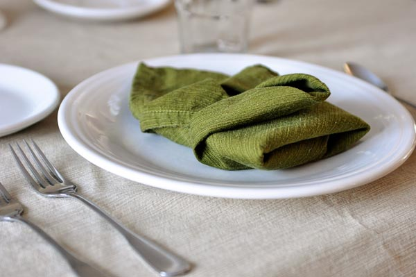 white plate with a green napkin folded on top