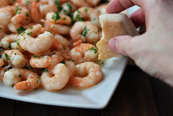 a platter of shrimp scampi with someone holding a half eaten roll over the top