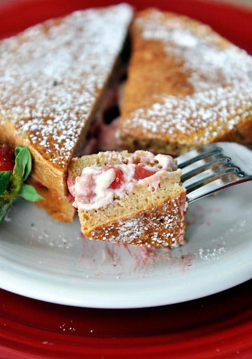 a strawberry cream stuffed french toast sprinkled with powdered sugar and a bite taken out