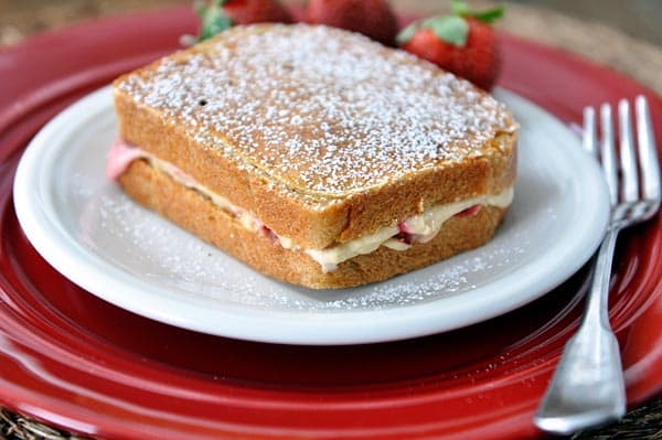 a stuffed french toast sprinkled with powdered sugar on a white plate