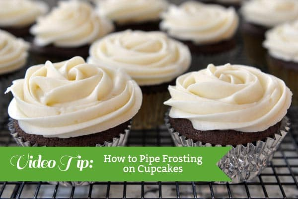 chocolate cupcakes with white piped frosting on a cooling rack