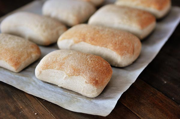light brown baked italian rolls lined up on a sheet of parchment paper