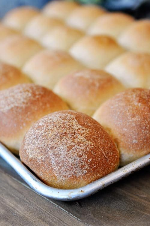 a cookie sheet full of golden brown cooked rolls