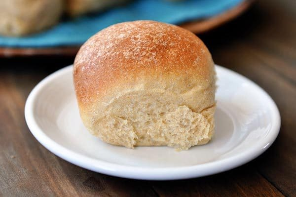 a golden brown whole wheat roll on a white plate