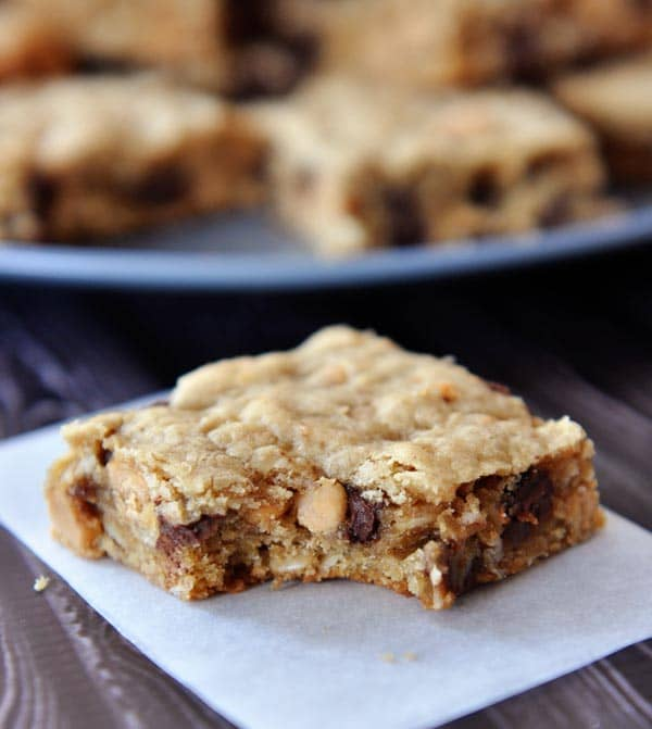 a chocolate chip peanut butter oatmeal bar with a bite taken out in front of a plate of other cut up bars