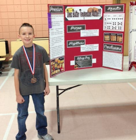 a little boy standing beside his science fair project